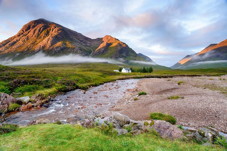 A beautiful cottage on the banks of the river Coupall and backed by the Buachaille Etive Mor mountains at Glencoe in Scotland @ Helen Hotson/Shutterstock