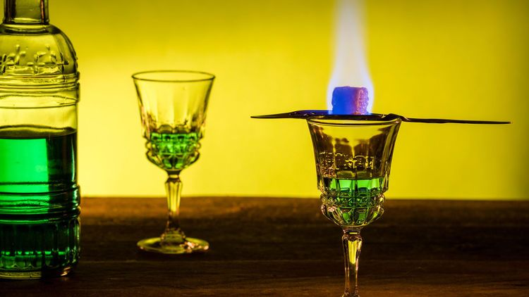 Bottle of absinthe and glasses with burning cube brown sugar © Cegli/Shutterstock