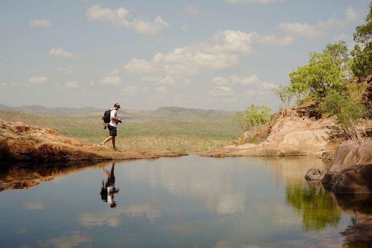 Australia, Gunlom, Tourist walking by pond