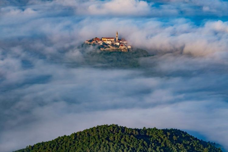 Ancient town Buzet with bell tower and old buildings flying above clouds. Unusual landscape of tourist destination in Istria, Croatia © Mny-Jhee/Shutterstock