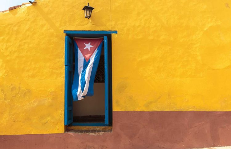 Travel Guide Cuba - Cuban flag in a doorway in Trinidad