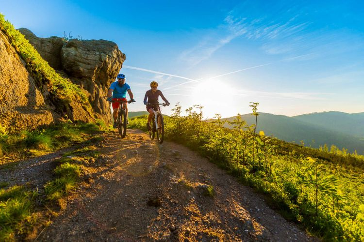 Cycling women and man riding on bikes at sunset mountains forest landscape.
