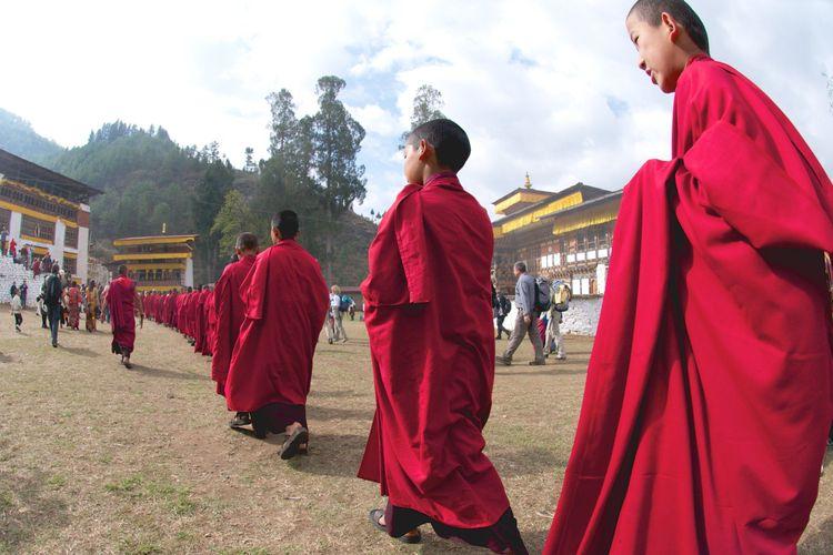 Monks walk in Monastery, Bhutan, Copyright Margot Raggett