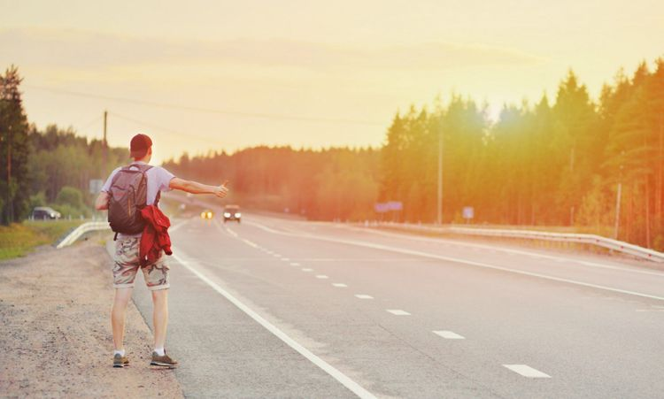 hitchhiking-catch-car-backpack-traveller-shutterstock_1351163843