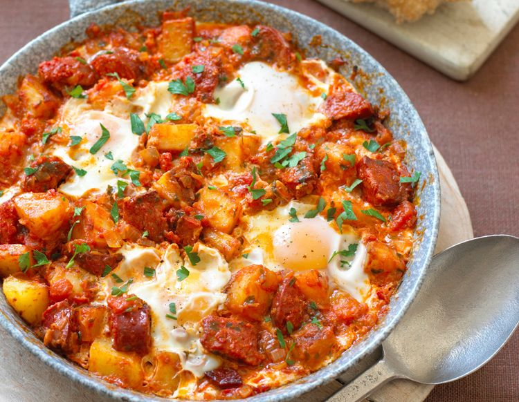 Huevos rancheros in heavy frying pan with bread and spoon, close-up