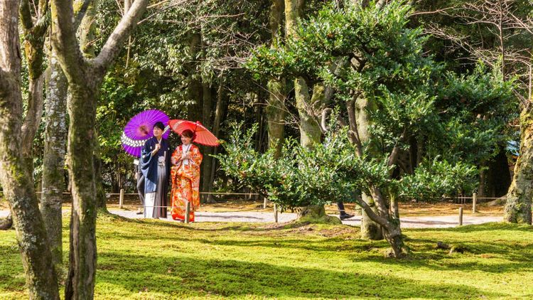 Couple dressed in kimonos walking in Kenrokuen Garden