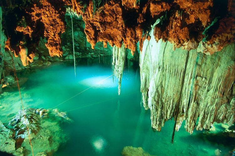 Mexico, Central America, The Yucat?n, Central Heartland, Cenote Dzitnup, limestone rock formations resembling stalactites above turquoise waters in natural cavern