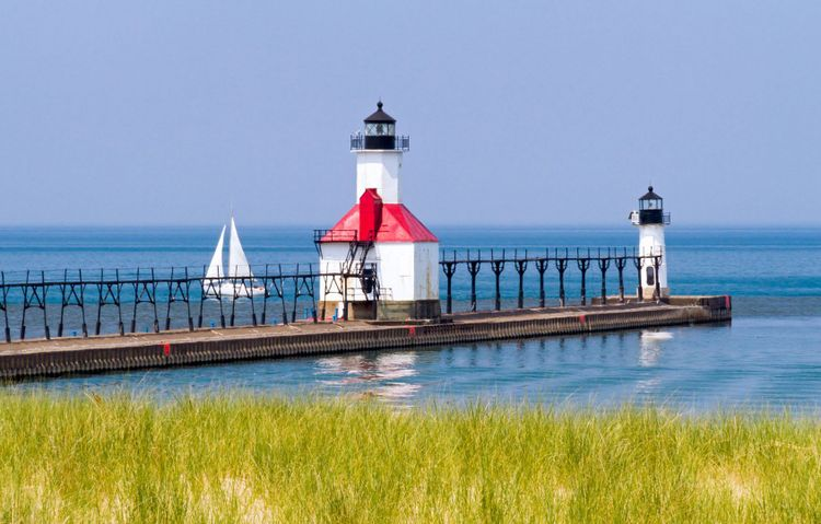 St. Joseph, Michigan North Pier Lighthouses with a Sailboat on Lake Michigan