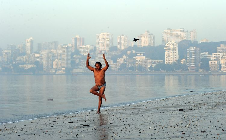 Morning walker Dileep Mahtre performs yoga on the Chowpatty beach in Mumbai.