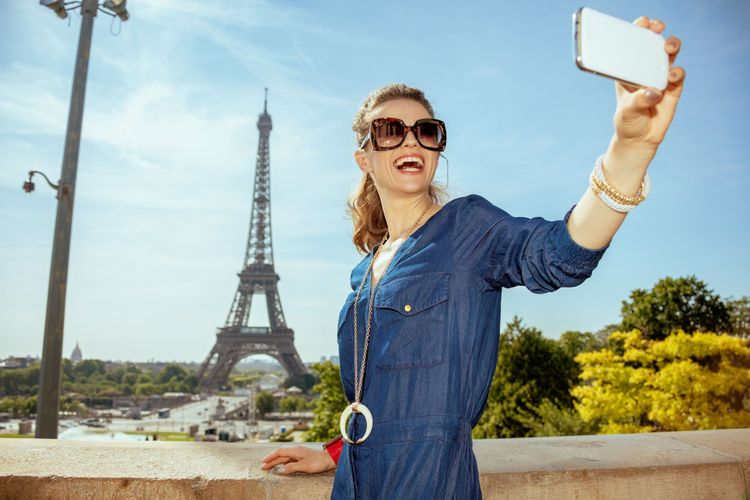 Taking selfie with phone at Trocadero overlooking Eiffel tower in Paris, France © Alliance Images/Shutterstock