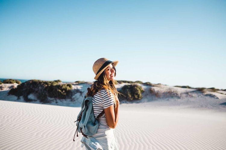 Smiling female solo traveller on sand dunes