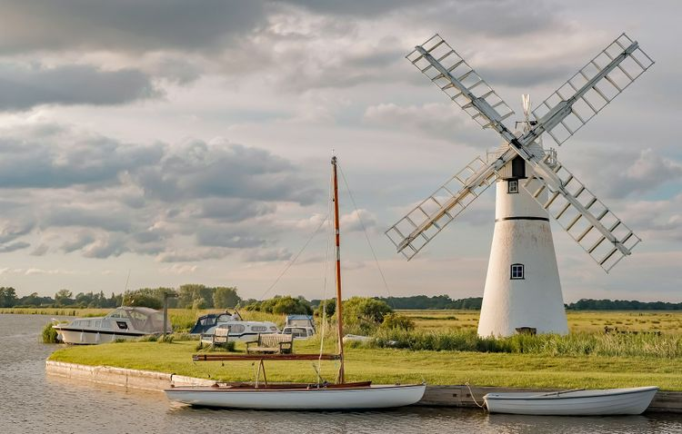 Thurne Mill on the waterside of Thurne River mouth in the Norfolk Broads @ yackers1/Shutterstock
